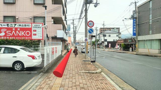 道の左側の歩道をまっすぐ進み、二つ目の信号まで行きます。